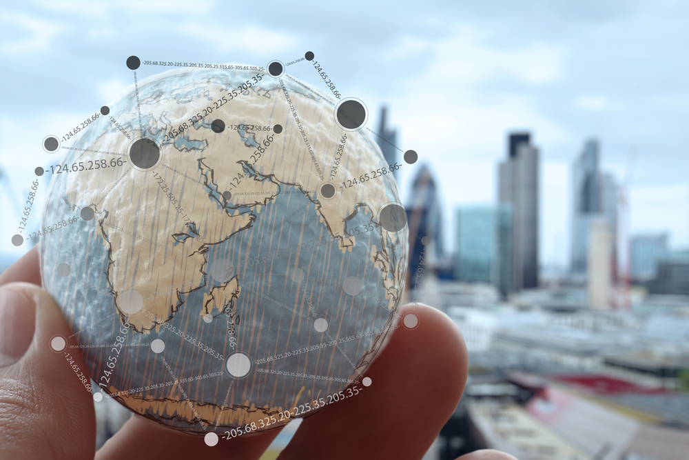 Globe of the earth in a man's hand with links all around it and a city skyline in the background